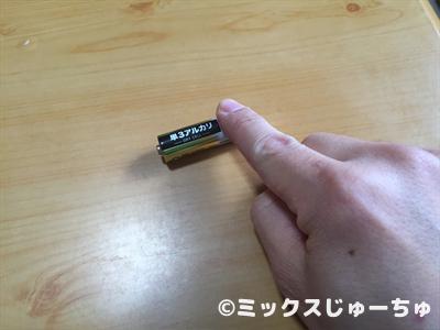 電池を指で弾いて回す2